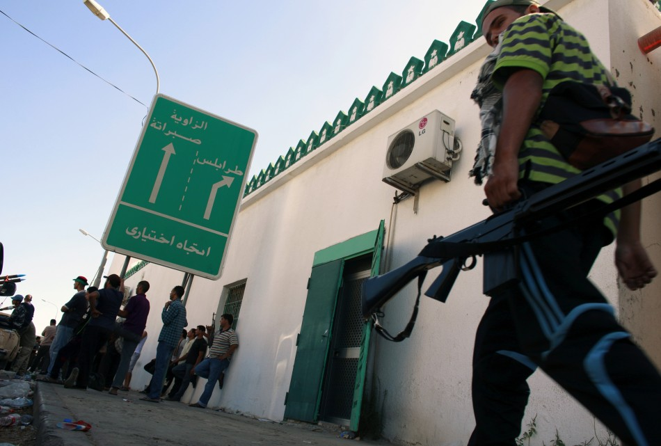 Rebel fighters sit near a road sign reading Tripoli after taking partial control of the coastal town of Zawiyah
