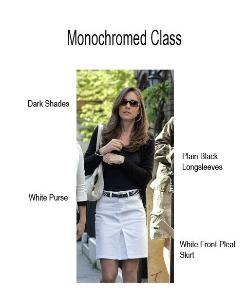 Kate in a simple black longsleeved top tucked in a white front-pleat skirt, with her waist accentuated by a thin belt.