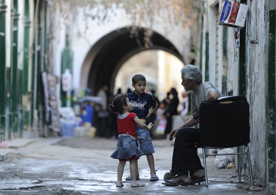 Children play with an old man in the Old City of Tripoli