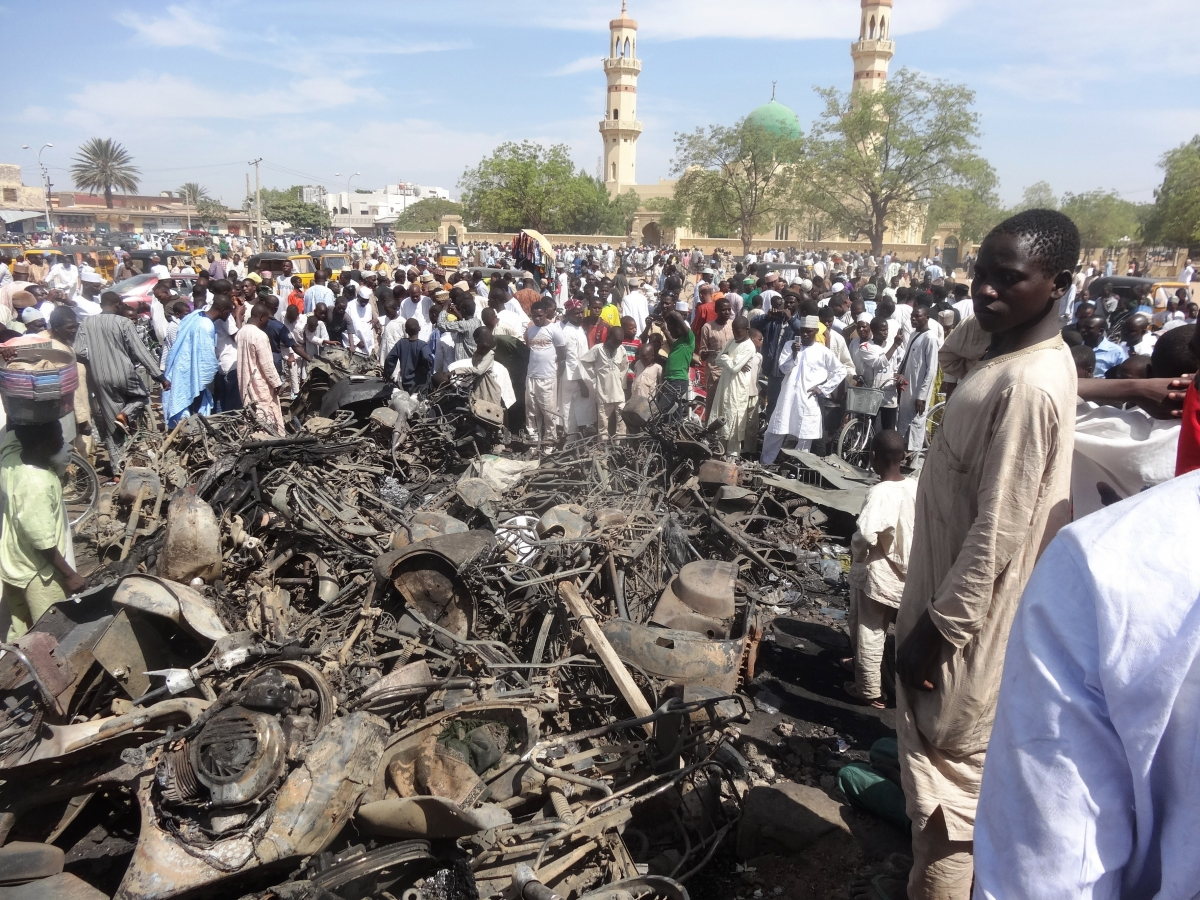 Residents look at a burnt motorcycles