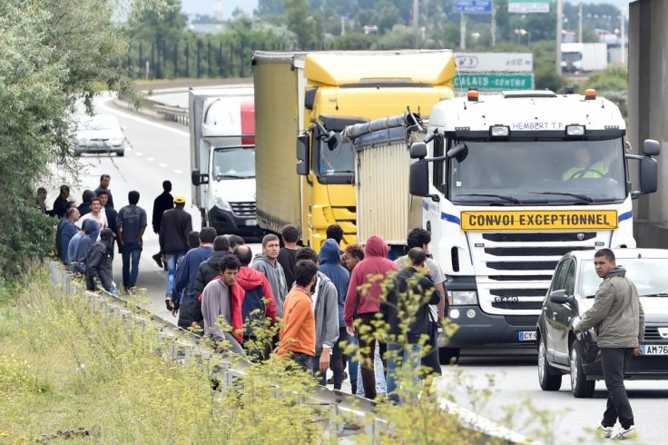 Migrants stand as lorries drive past