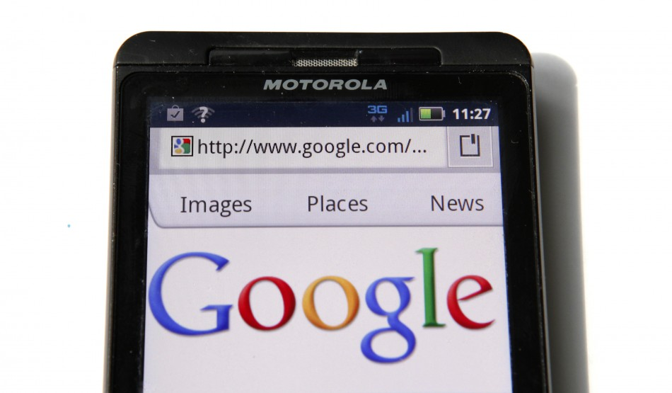 A Google homepage is displayed on a Motorola Droid phone in Washington