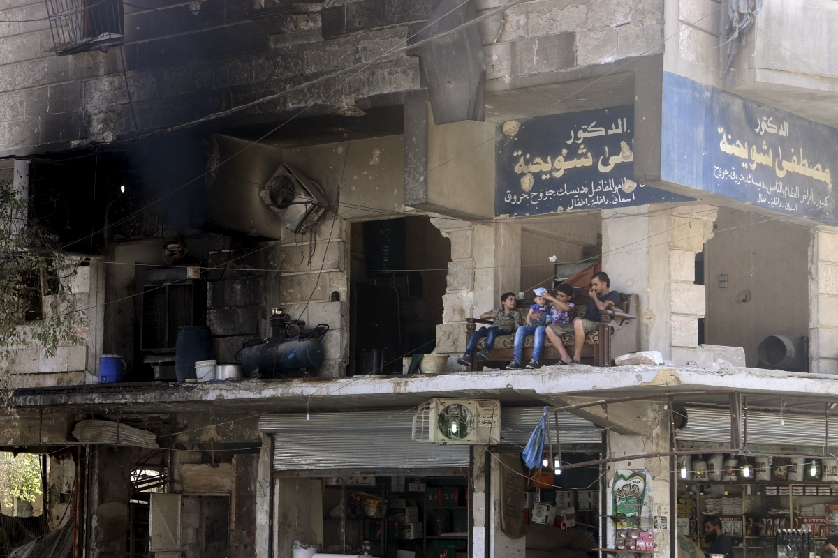 Aleppo resident sit outside damaged building