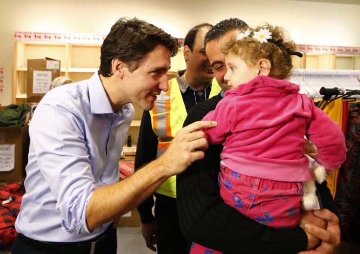 Syrian refugees are greeted by Justin Trudeau
