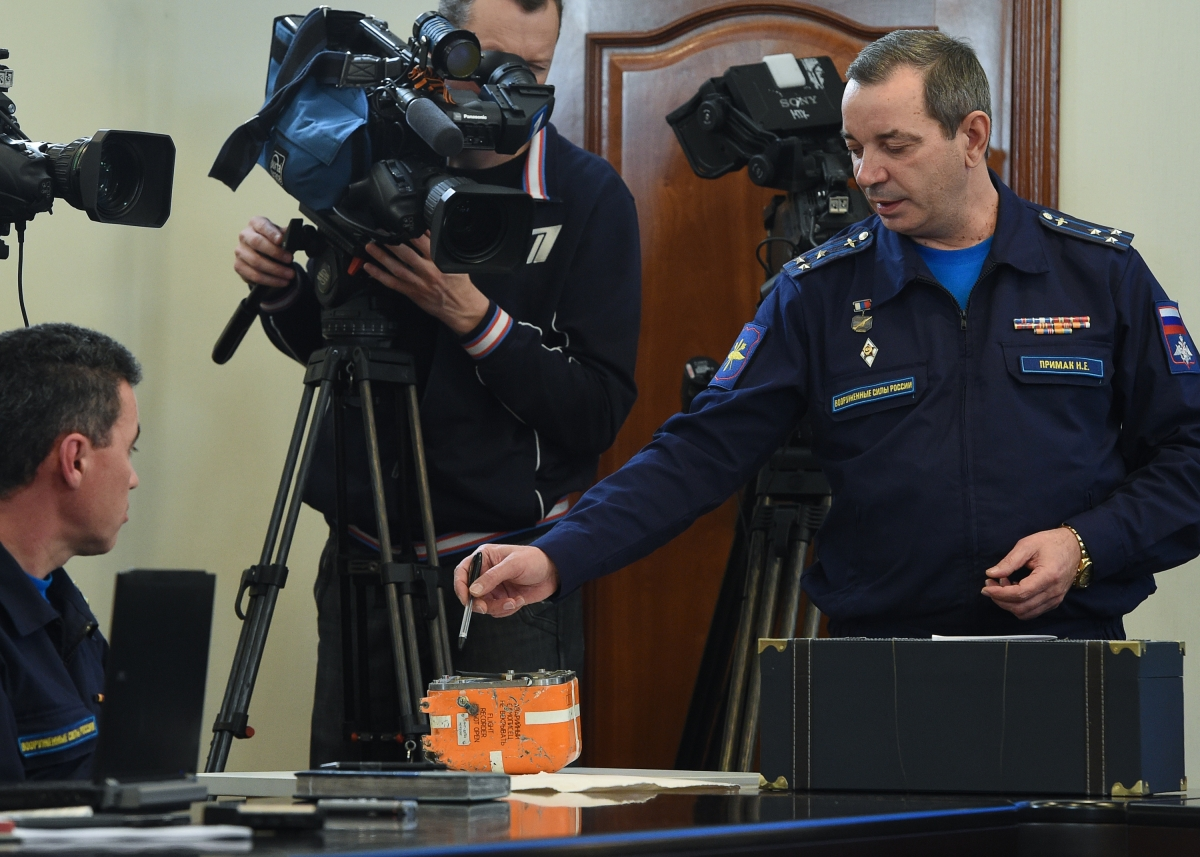 A Russian military official points to the flight recorder from the Russian Sukhoi Su-24 bomber which was shot down by a Turkish jet on November 24