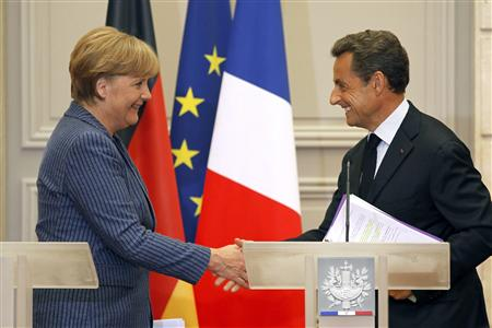 France's President Nicolas Sarkozy (R) shakes hands with German Chancellor Angela Merkel