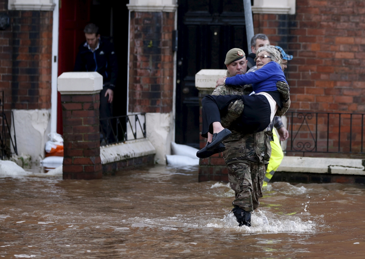 soldier carries woman out of flooded house
