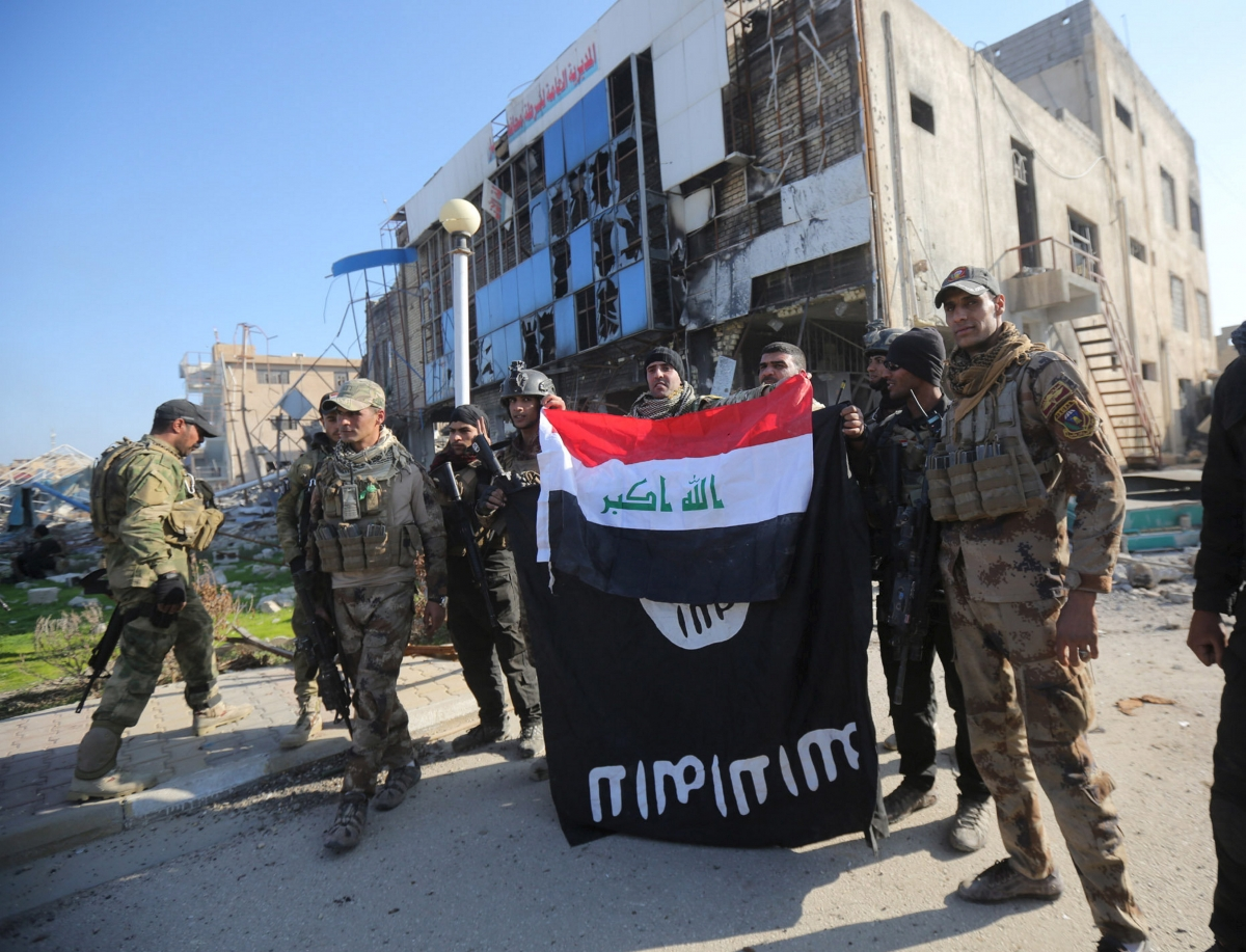 Iraqi security forces hold an Iraqi flag