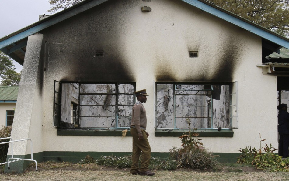 A Zimbabwean policeman walks past the burnt out home of retired army general Solomon Mujuru in Beatrice Farm