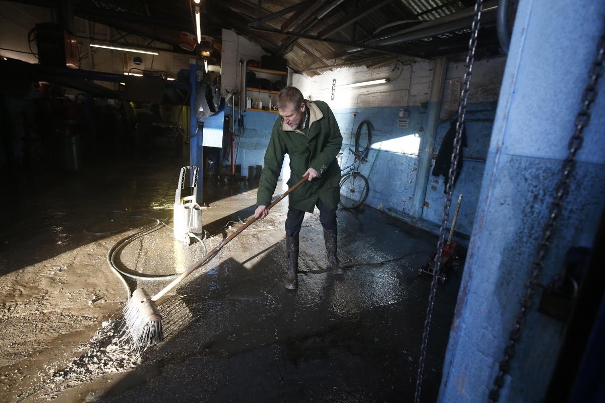 man cleans after york floods