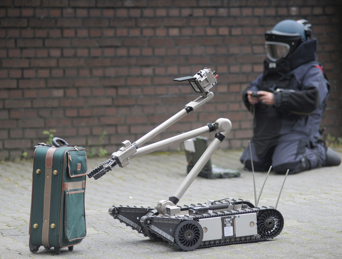 Remote-controlled robot inspects suitcase for bombs