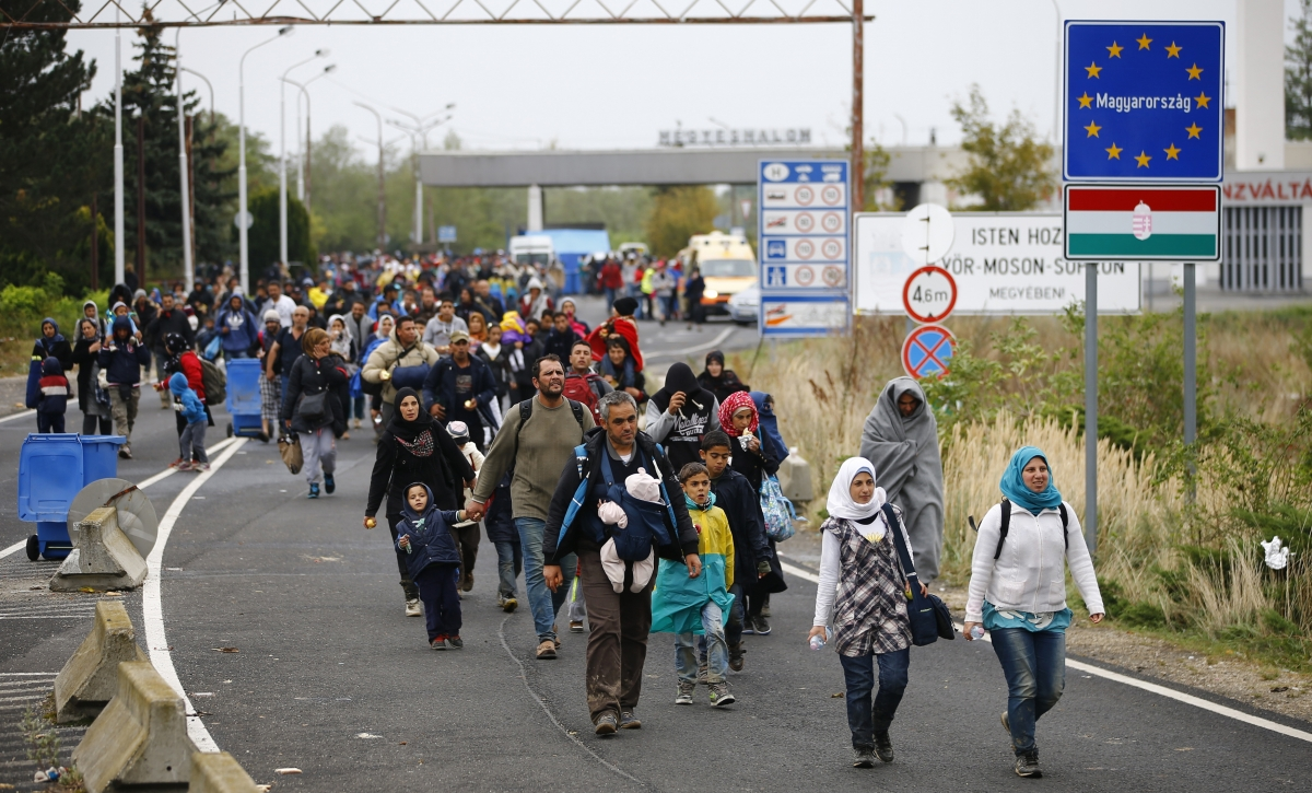 Migrants walk as they cross the border from Hungary