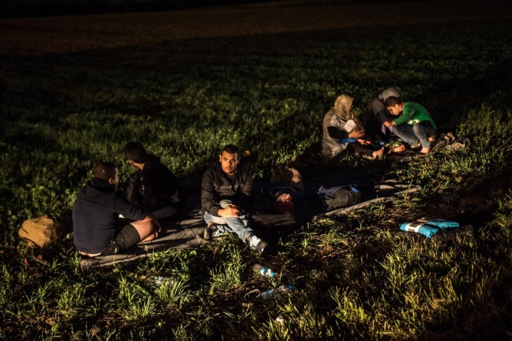 Migrants rest by the road
