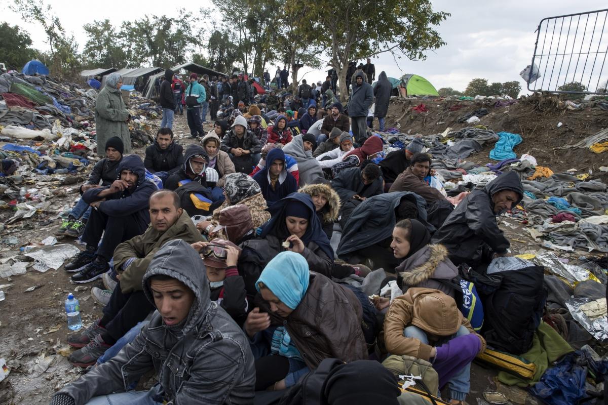 Migrants sit along a road
