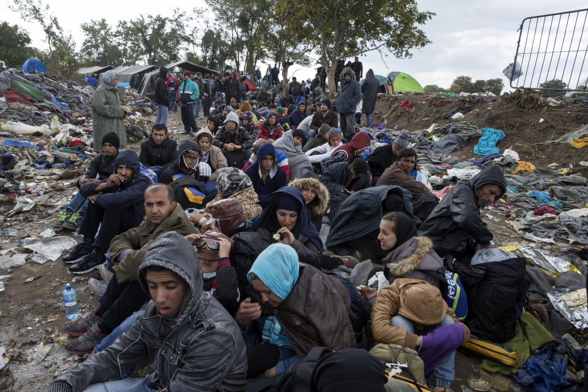 Migrants sit along a road