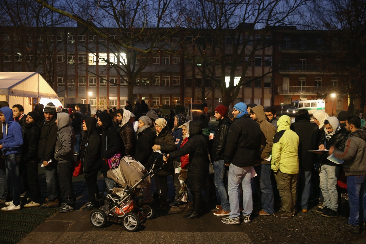 Refugees and migrants queue to register atanasylumcentre