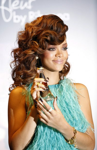 Singer Rihanna poses with a bottle of her fragrance quotReb039l Fleurquot at its launch at a House of Fraser department store in London