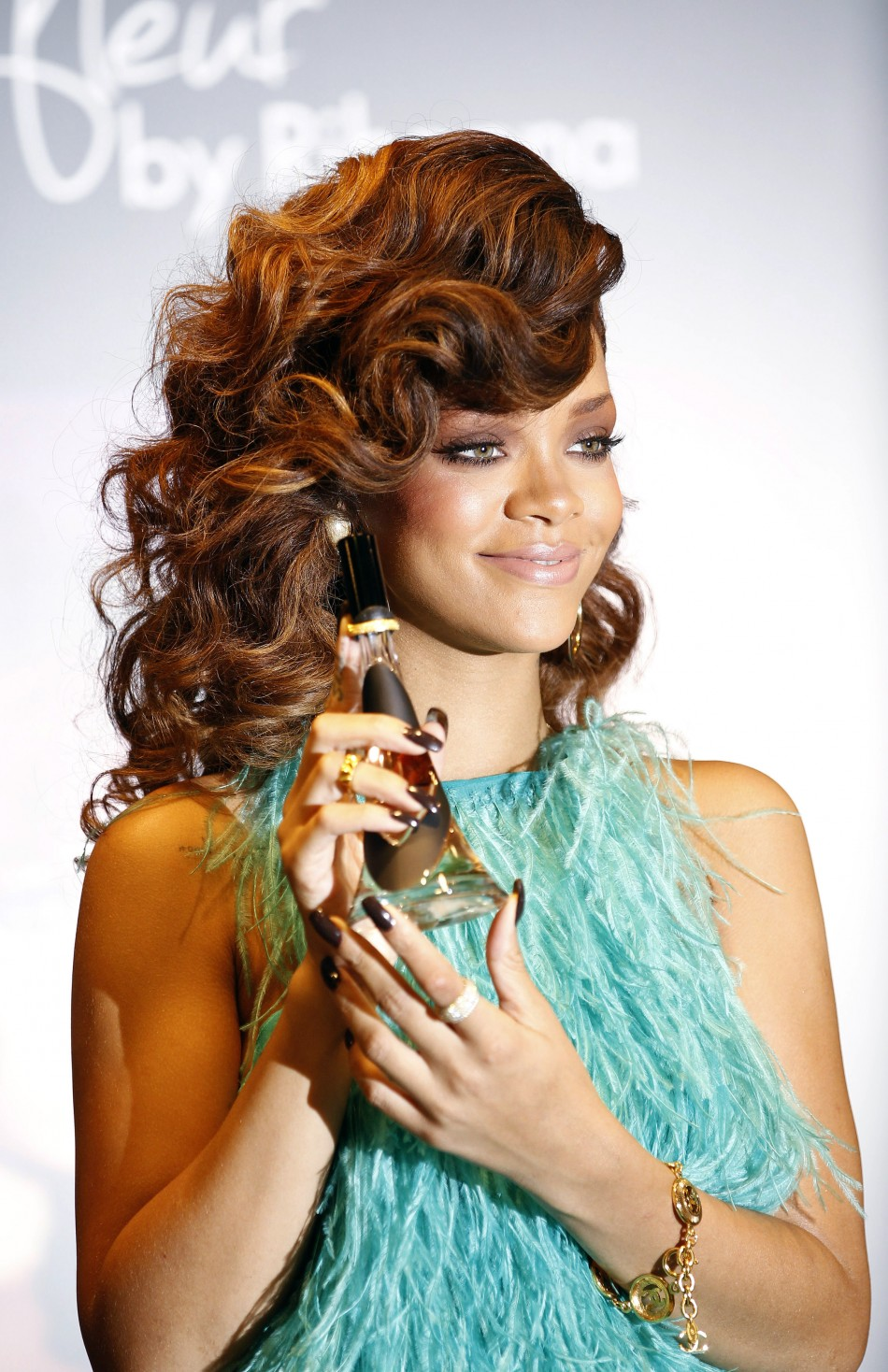 """Singer Rihanna poses with a bottle of her fragrance """"Reb'l Fleur"""" at its launch at a House of Fraser department store in London"""