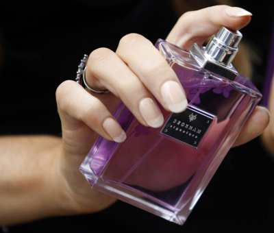 A woman sprays perfume from a bottle of Victoria Beckham039s 039Signature039 fragrance at Harvey Nichols in Manchester