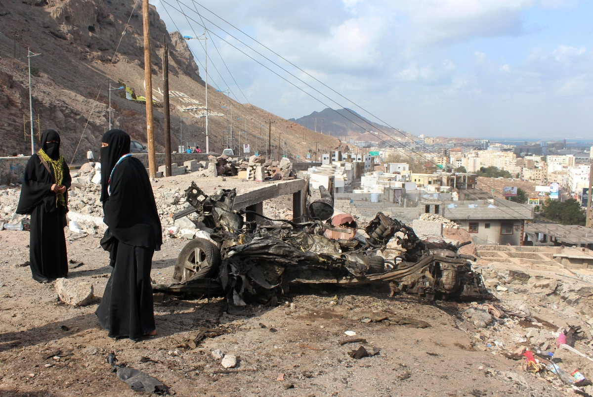 Yemeni women stand next to the remains of a vehicle