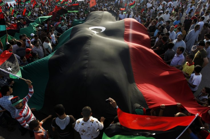 Protesters carrying a Libyan flag