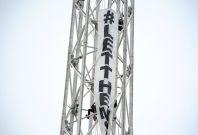 Protesters climb a spire