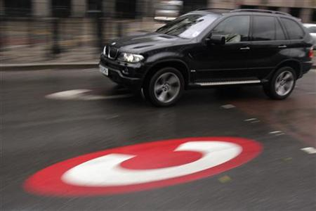 A large vehicle drives past a symbol for the Congestion Charge in London
