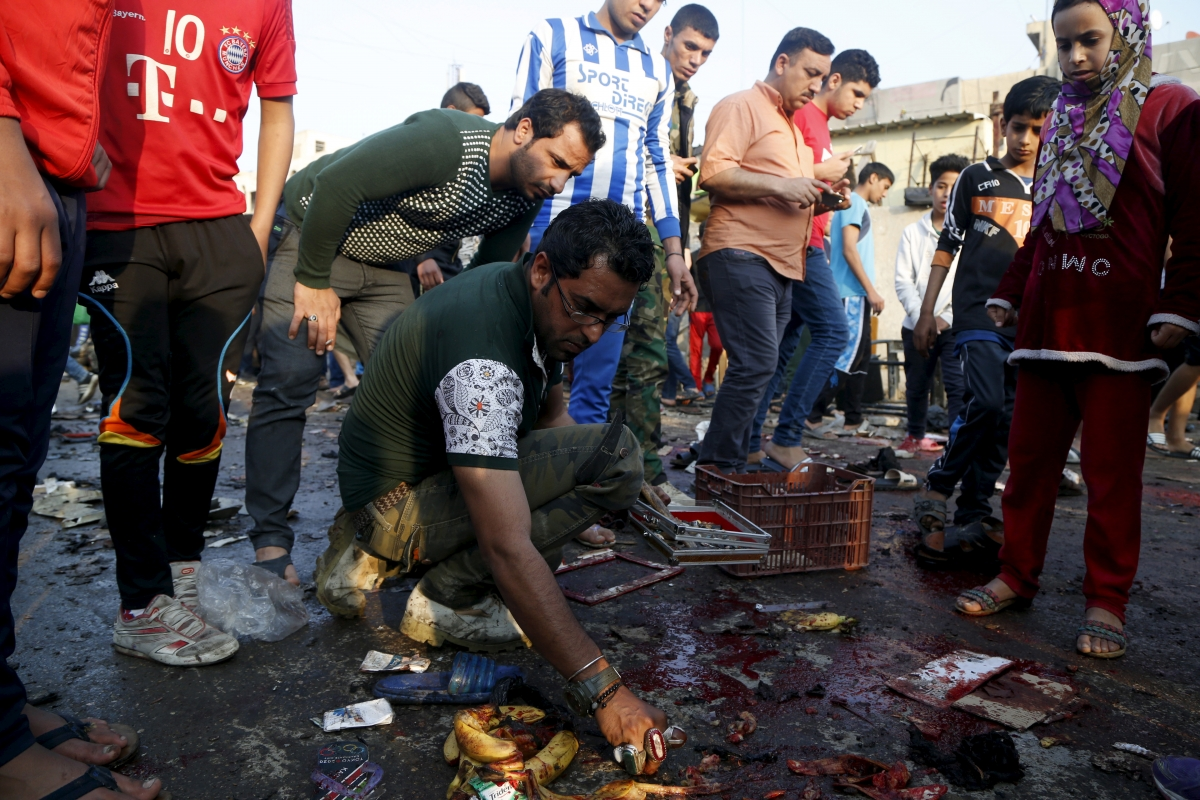 People gather at the site of suicide blasts in Baghdad