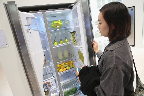 A woman looking at a fridge