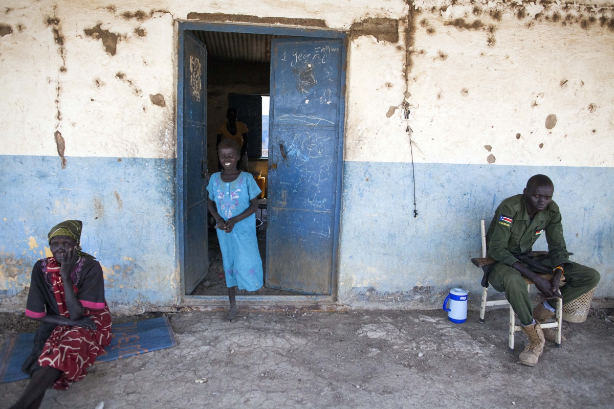 A woman and a girl from the Dinka community are pictured next to a soldier in the Sobat Secondary School in Malakal, on February 26, 2016ALBERT GONZALEZ FARRAN/AFP/Getty Images
