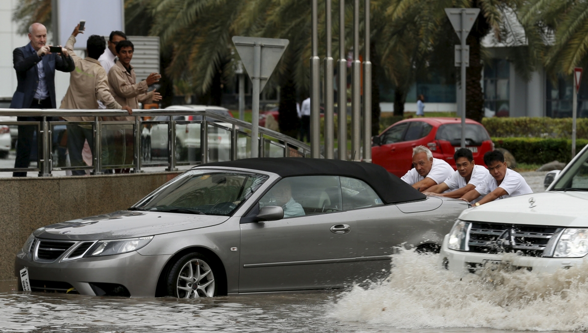 People in Dubai push car through flood