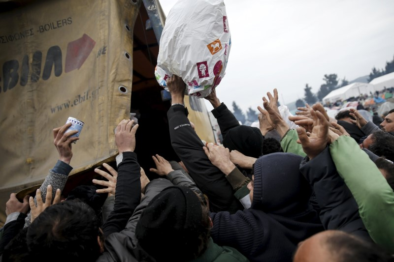 Refugees rush a food truck