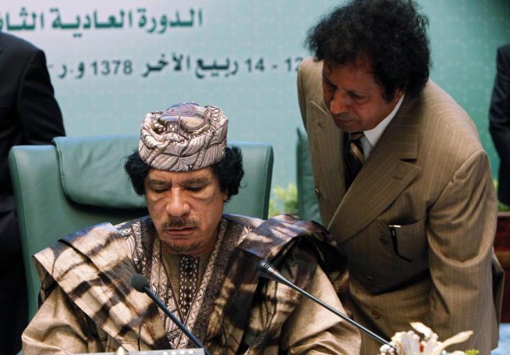 Muammar Gaddafi (L) listens to Ahmad Gaddaf al-Dam