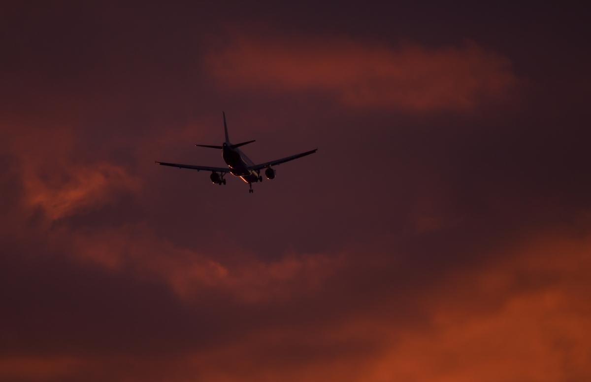 A passenger aircraft makes its landing approach at dusk
