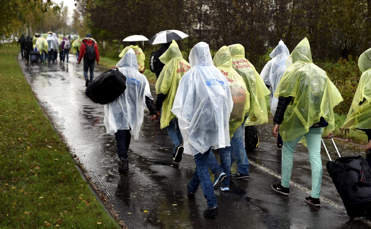 Refugees walk through the pouring rain from a public transport centre to the Lappia-building refugee reception centre in Tornio, northwestern Finland,