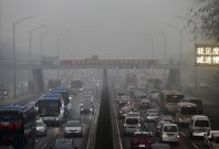 Vehicles are seen on a street amid heavy smog in Beijing