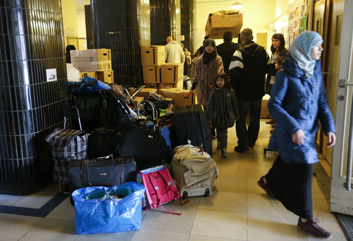 Migrants carry their goods upon their arrival at a refugee shelter in Berlin