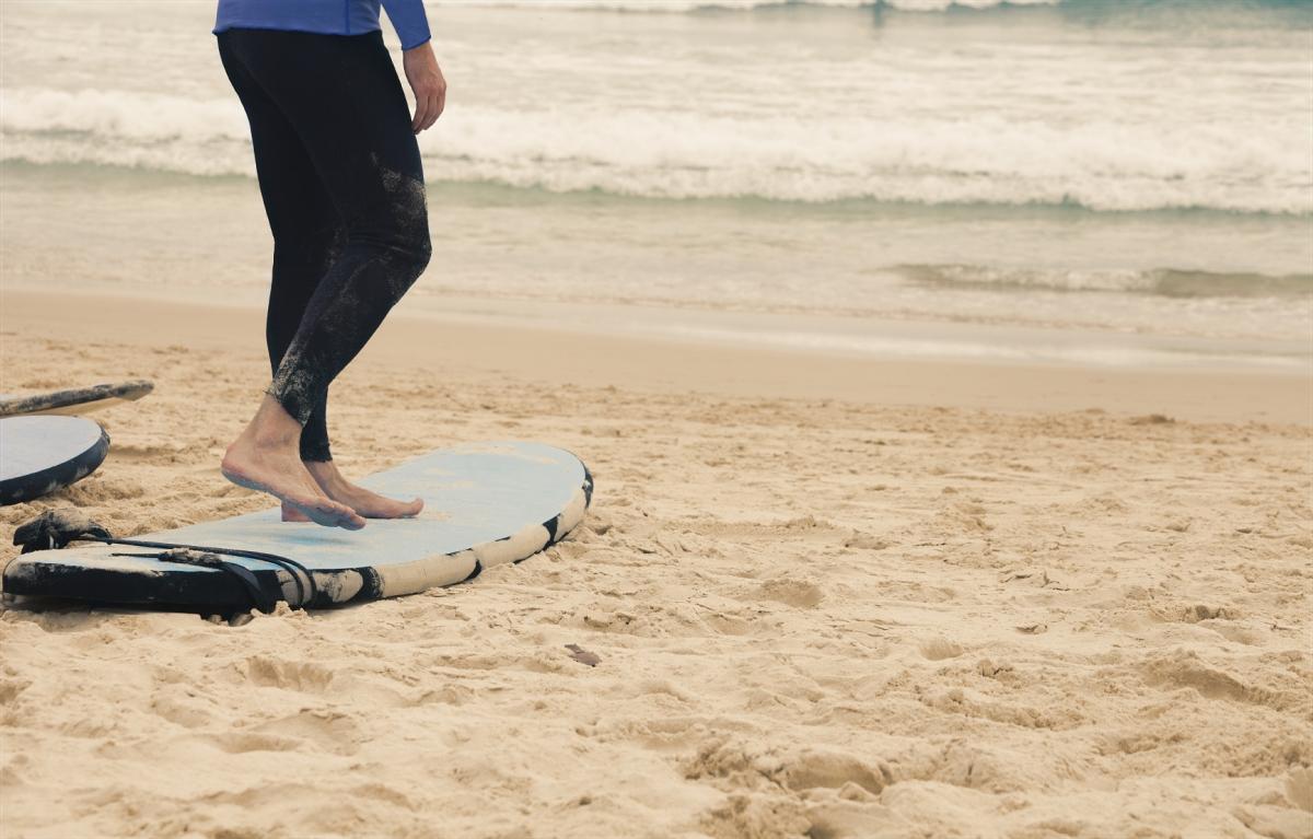 A surfer prepares on the beach