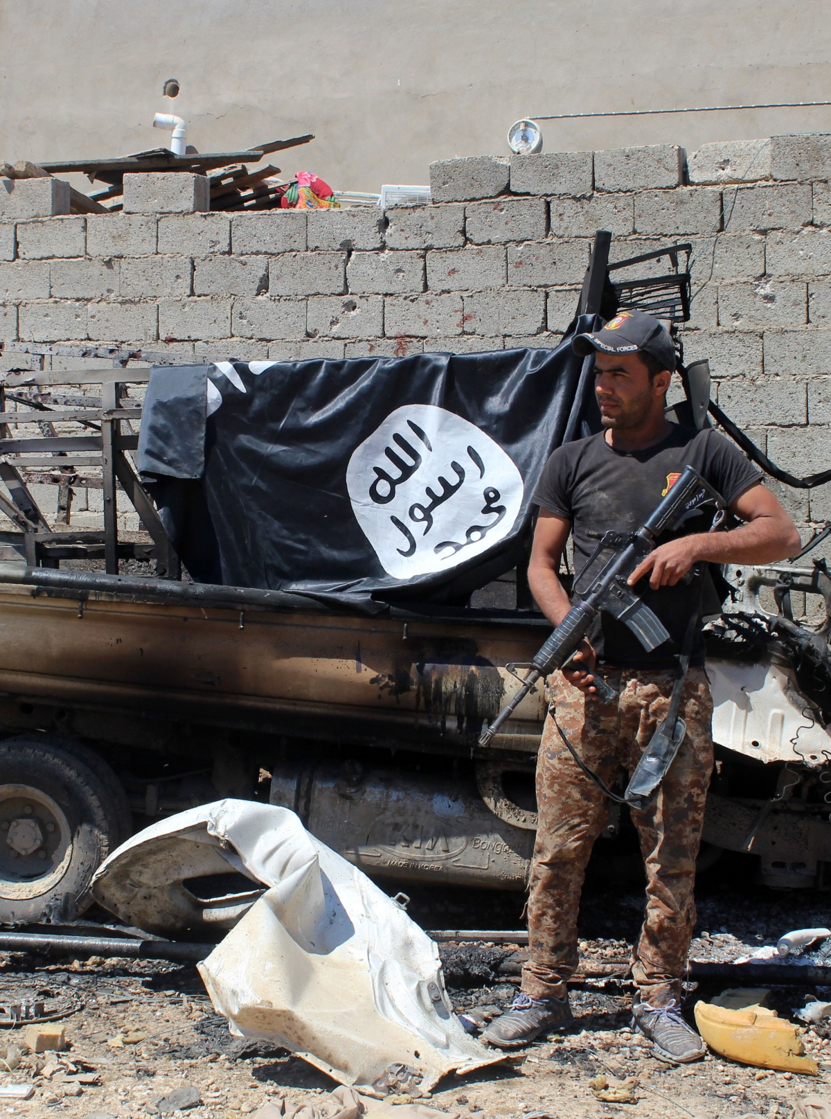 A member of Iraqi government forces inspects a burnt vehicle with on its top a flag of the Islamic State group (IS) after they retook an area from its jihadists on April 2