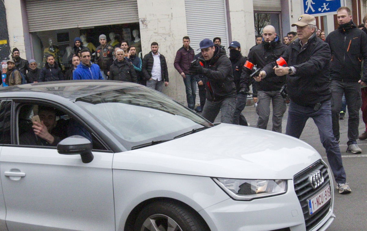 Belgian police point their guns at a car driving towards a police road block before it hit and injured a woman on the street in the Brussels district of Molenbeek,