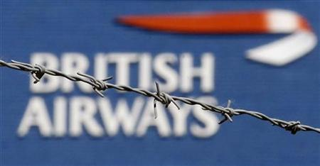 The British Airways logo is seen behind barbed wire at Heathrow Airport, west of London