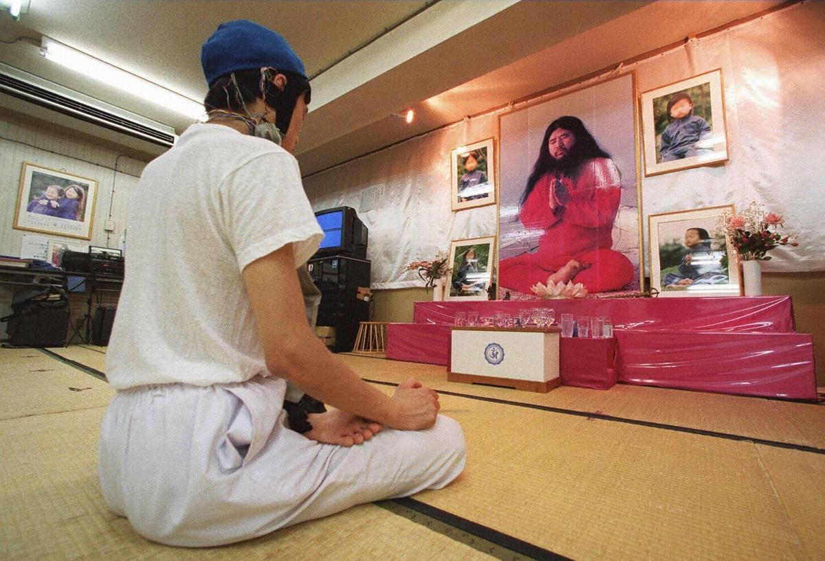 a follower meditating before portraits of Aum Supreme Truth guru Shoko Asahara