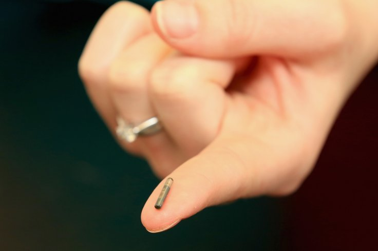 A microchip held out by a nurse