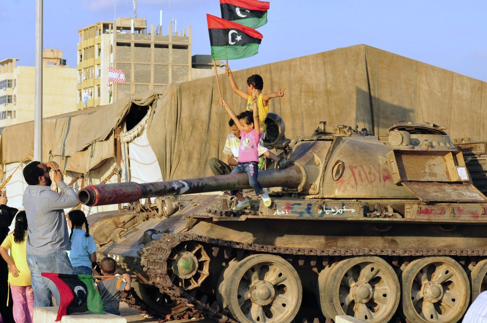 Libyan children sit on a tank while waving Kingdom of Libya flags near the court house in Benghazi