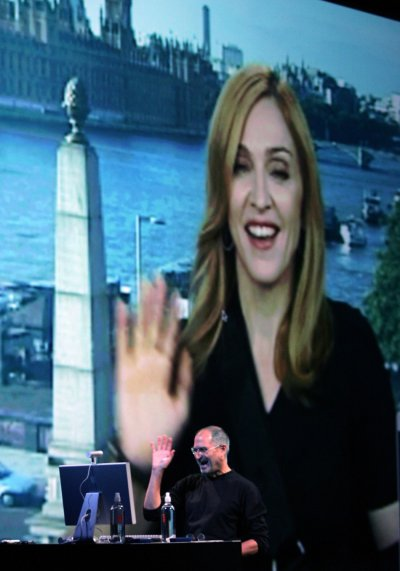 Apple CEO Steve Jobs waves back to Madonna as she waves from London during a conference call at an event in San Francisco
