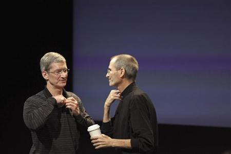 Apple COO Tim Cook and CEO Steve Jobs remove their microphones after a news conference at Apple headquarters in Cupertino