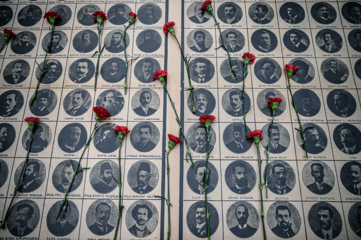 People lay red carnations