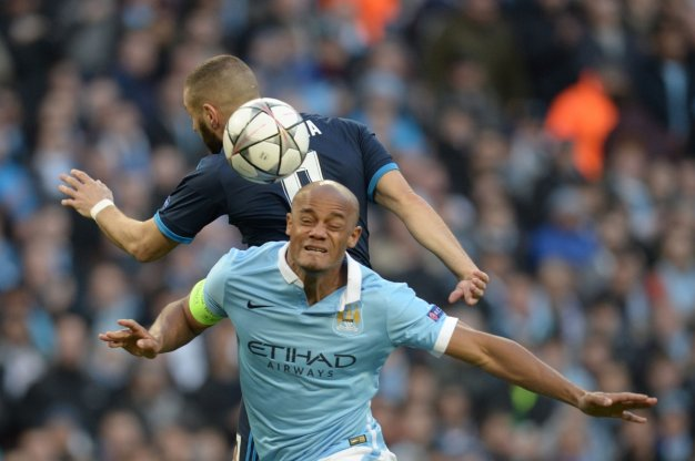 Vincent Kompany heads the ball