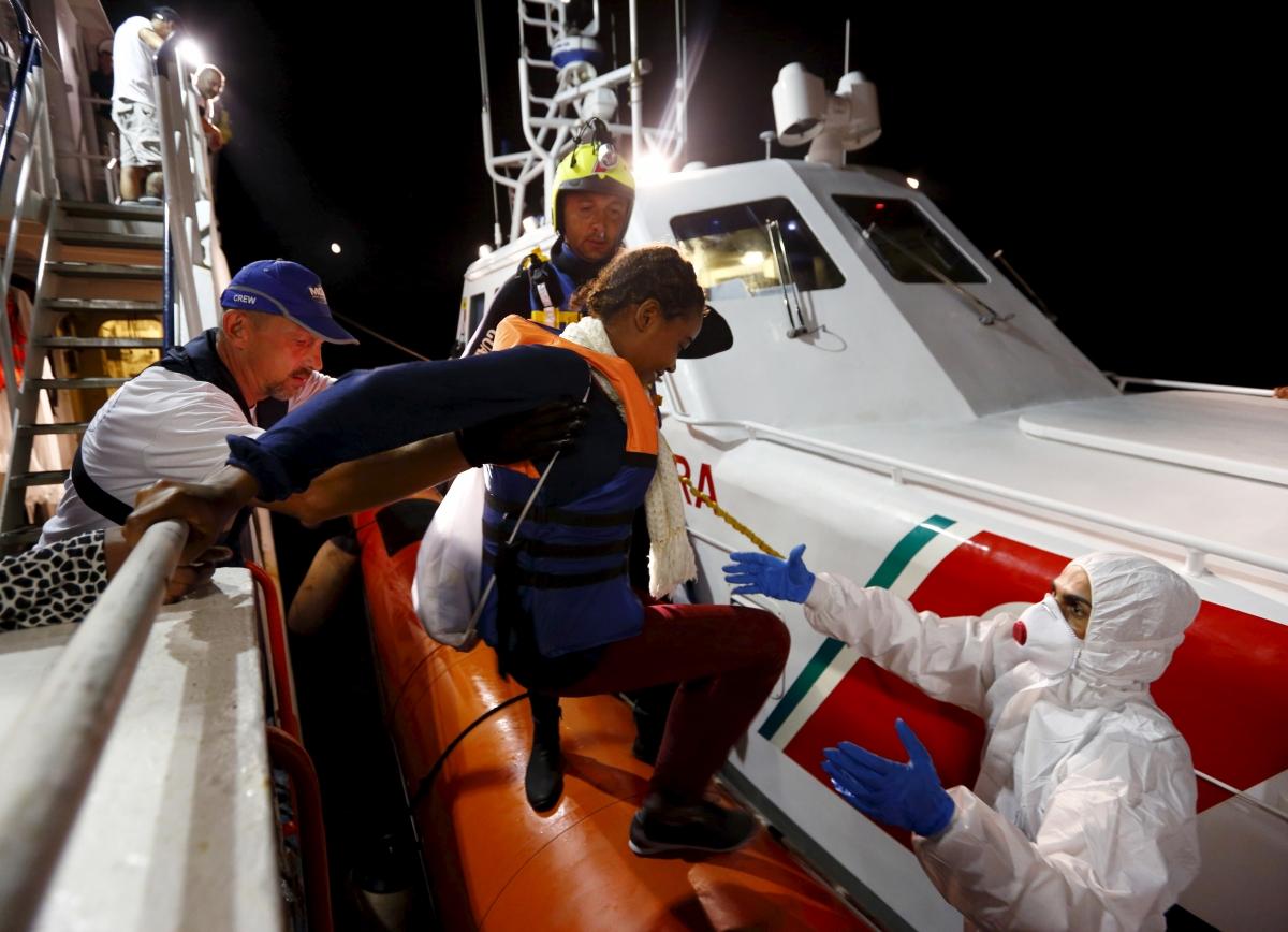 A migrant boards a coast guard vessel