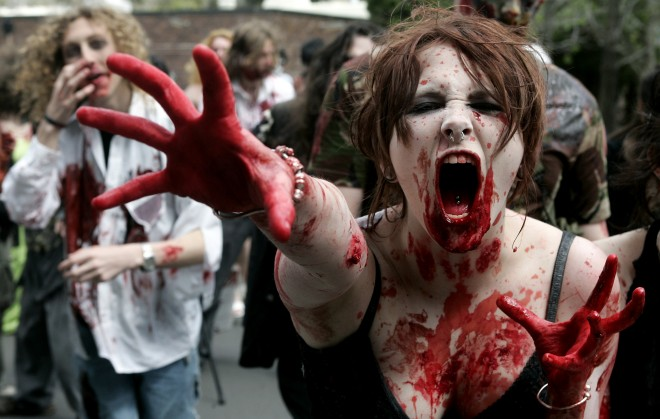 """University students made up to look like zombies take part in a bid to break the world record for the """"biggest zombie lurch"""" in Sydney"""